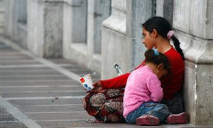 A woman begs with her child in Athens, Greece. Some 70 percent of Greek children live in jobless households.