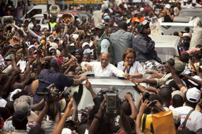 Haiti's former President Jean-Bertrand Aristide waves to supporters as he campaigns with presidential candidate Maryse Narcisse of the Fanmi Lavalas political party, in Petion-Ville, Haiti, Monday, Aug. 29, 2016.