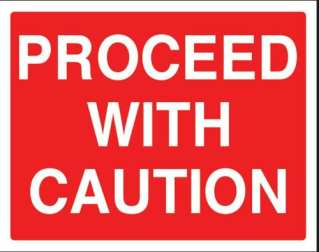 A red road sign that says proceed with caution, signifying taking care when working with nano- technology