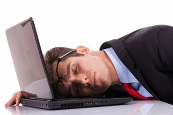 Male dressed in work attire sleeping on his open computer laptop