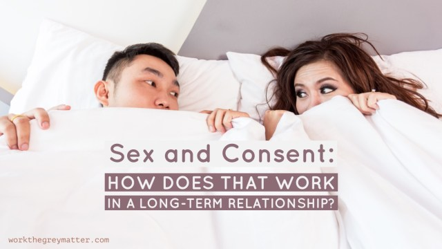 Picture of a man and woman lying next to each other in bed, half-hiding under duvet, looking at each other excited, with the words: sex and consent: how does that work in a long-term relationship? workthegreymatter.com