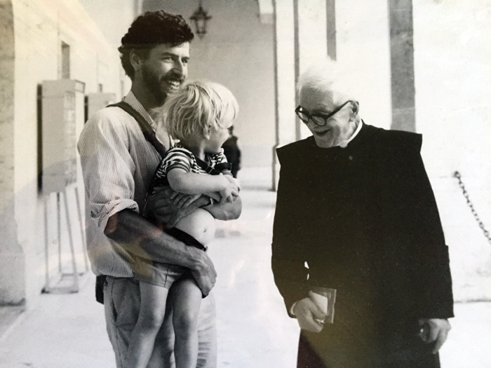 black and white photo of Richard Hodges, carrying child in his arms, and Don Angelo Pantoni