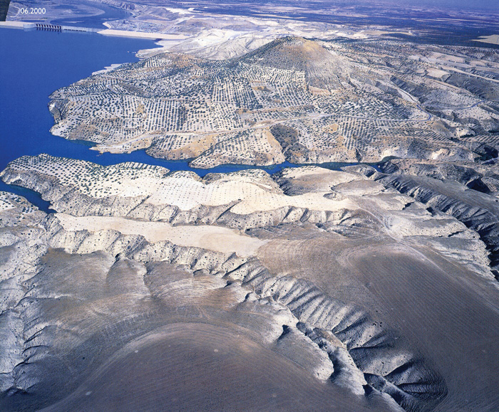 Aerial view of the site of Zeugma, with the new dam shown across the water top left. Pistachio orchards speckle the hillside.