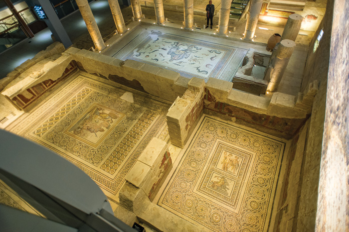 View of reconstructed rooms in the house of poseidon, with mosaics on the floors, and fragments of wall