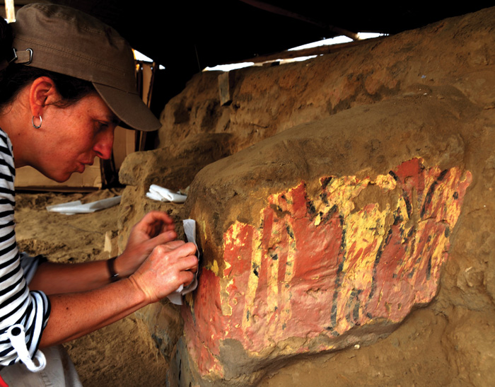 Conservator works on wall-painting at Pachacamac, which shows a yellow figure outlined in black, on a red background