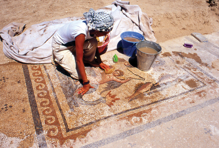 Archaeologist cleans one of the figured mosaics