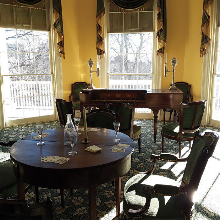 Restored room inside house with chairs, table, and piano