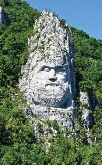 Sculpture of Decebalus carved into rocks by the river