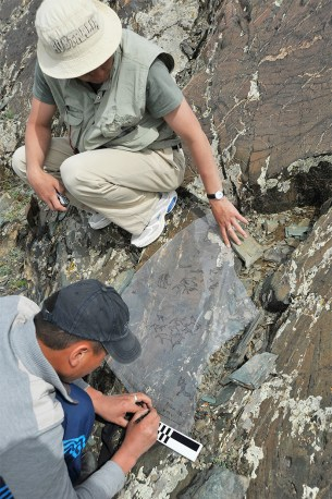 Two researchers crouched on a rock-face, one is holding a transparent plastic sheet over the petroglyphs on the rock while the other traces them.