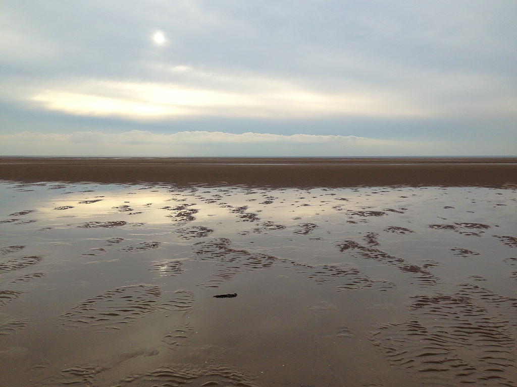 Lytham St Anne's beach with sunlight reflecting on the surface water