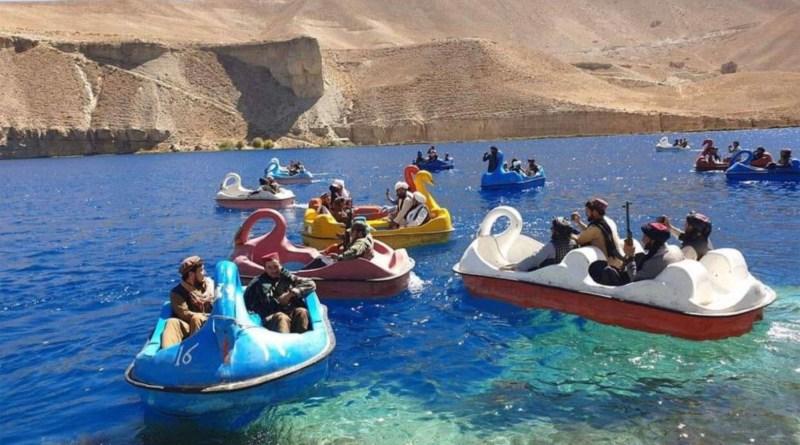 Combatientes armados talibanes son vistos montando botes a pedales en un lago en Afganistán