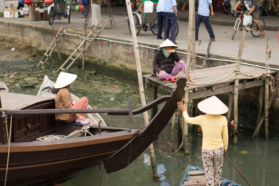 Vietnamese women in cone hats talking on boat deck and boats