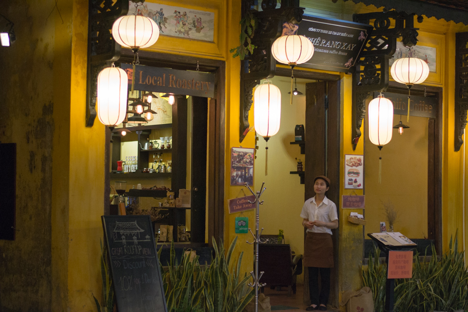 Vietnamese waitress waiting at the door to welcome guests