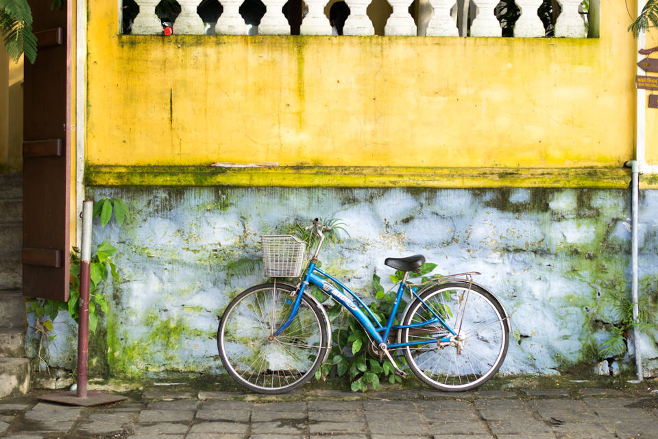 Blue bicycle against yellow and blue wall