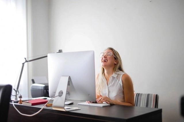 Coronavirus Memes Making A Young Blonde Woman Laugh As She Sits At Her Desktop Computer In Her Home Office.