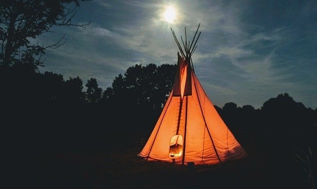 Nighttime photo of orange teepee with light inside in the woods