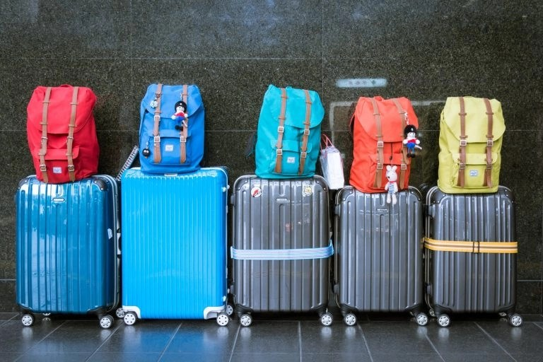 Suitcase Or Backpack? Five Colorful Backpacks On Tops Of Five Suitcases