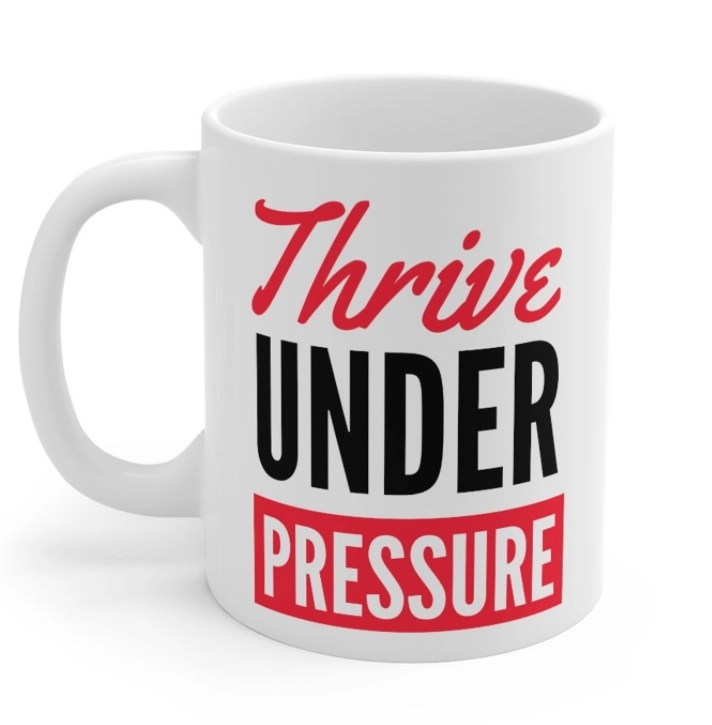 White Etsy mug with thrive under pressure written in black and red text
