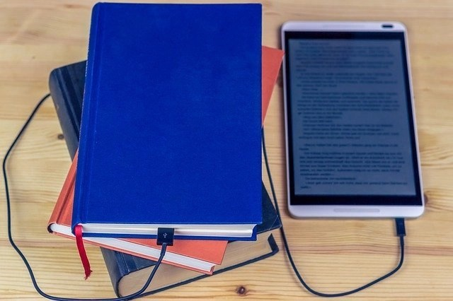 Blue hardback book on top of 2 other books with a tablet on the right side with a charging cable leading from the tablet to the blue book