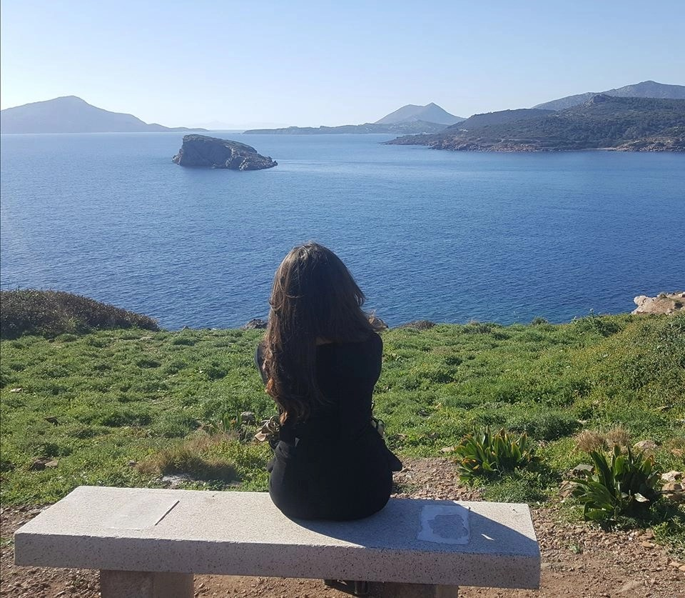 The digital nomad lifestyle for Melissa Douglas, sitting on a stone bench overlooking the water dotted with islands in Greece