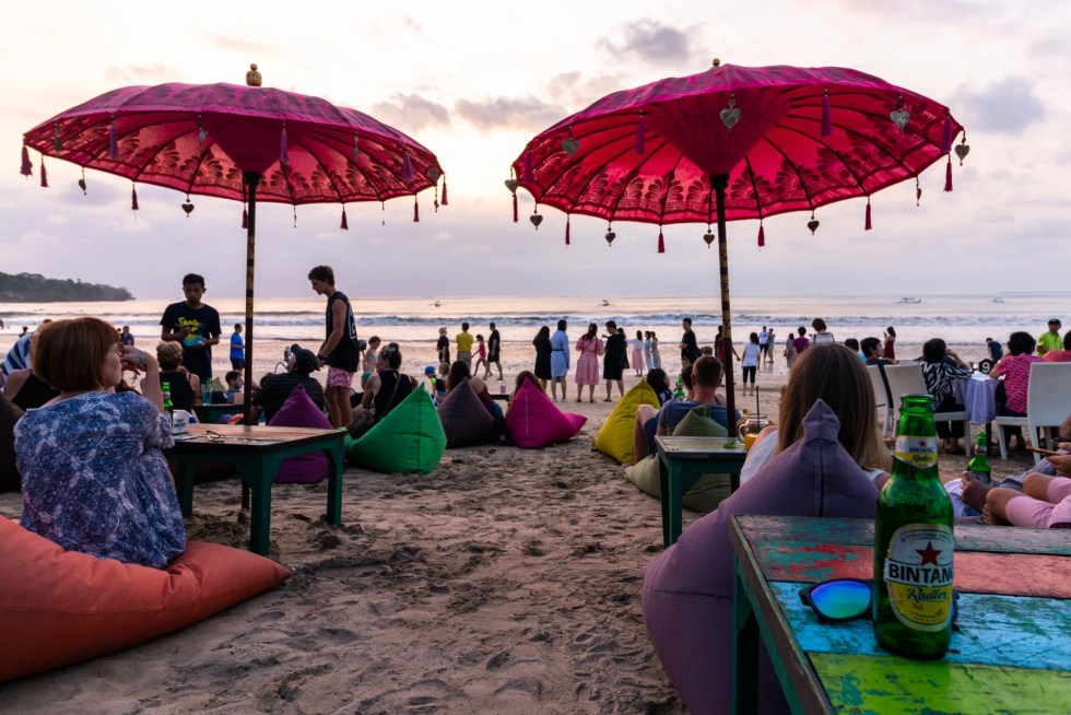 The digital nomad lifestyle in Indonesia with 2 red beach umbrellas, a Bintam beer on a table and many people standing on a beach at sunset
