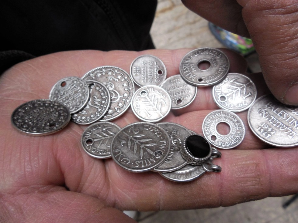 Man holding old Palestinian coins in the palm of his hand in the Middle East marketplace in Hebron, Palestine