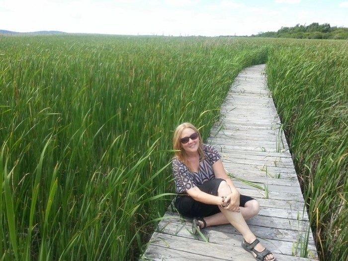 Woman sitting on wooden path in grass
