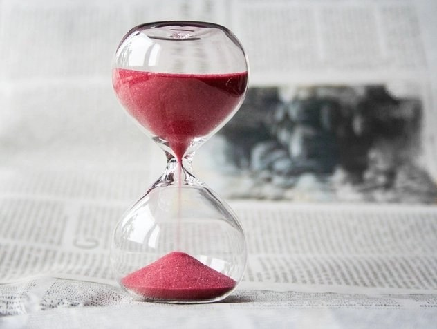 Red sand flowing through hourglass to keep track of time so you can be someone who tries and succeeds