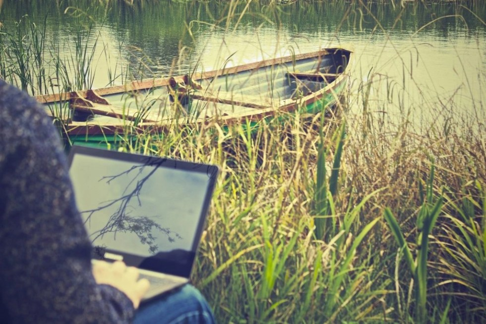 Man working remotely on a laptop alongside a canoe in a lake