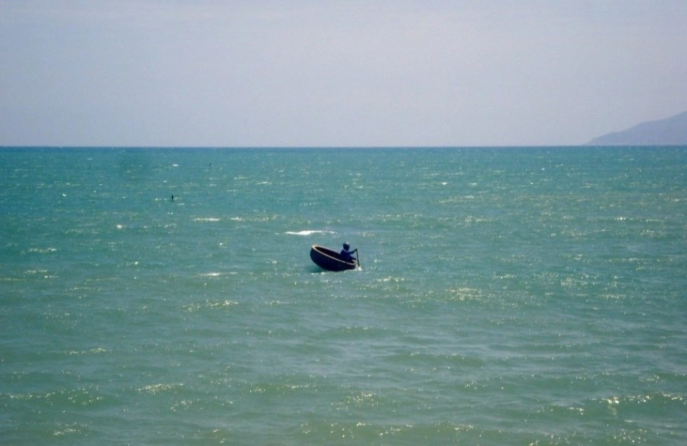 Man in a round boat in the South China Sea as seen in Nha Trang, Vietnam