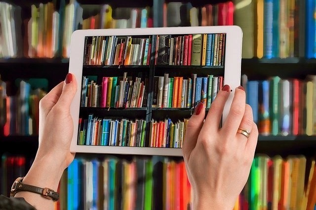 Woman's hands holding white iPad taking a photo of colorful blogging courses books on a bookshelf