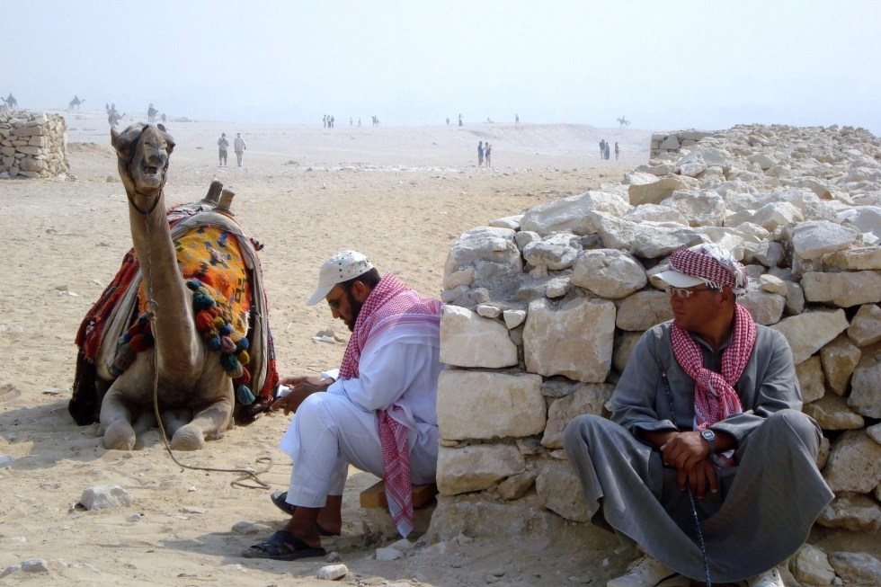 Two men and a camel resting against a stone wall on the ground at the Pyramids of Egypt at Giza