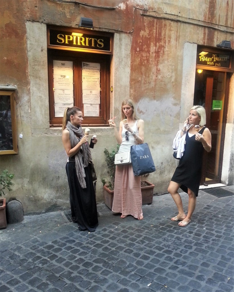 3 women standing on a cobblestone street in Rome