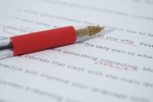 Red pen and paper for earning income as a proofreader, one of the best-paying work-at-home jobs for retirees