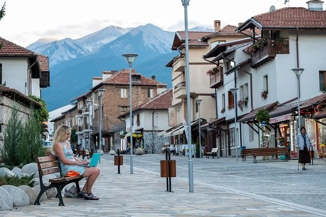 Woman traveler working on a bench in a European town with snow-capped mountains in the background