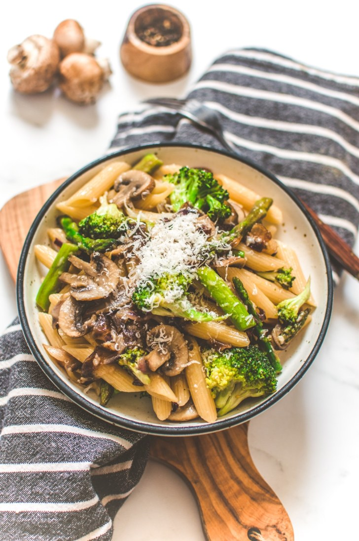 Pasta Dish Served with Vegetables on a Bowl topped with Grated Vegan Cheese