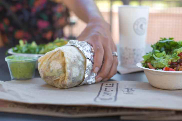 Woman Eating a Vegan Chipotle Burrito at the Outdoor Tables of the Restaurant