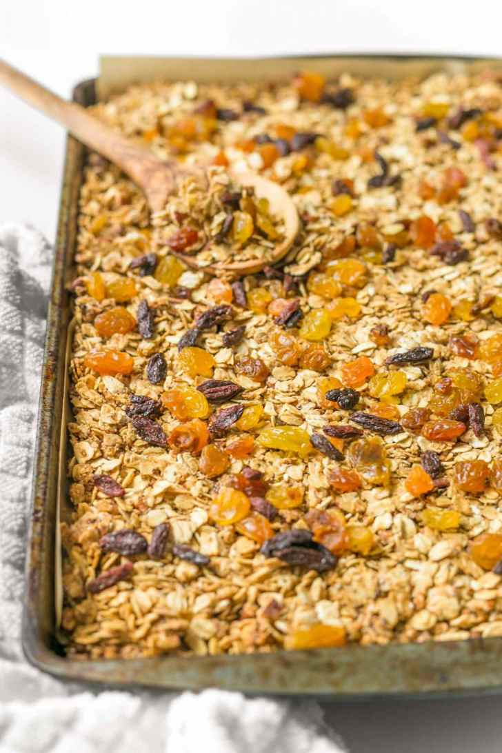 Baking tray with vegan homeamde granola with a large wooden spoon on a white surface