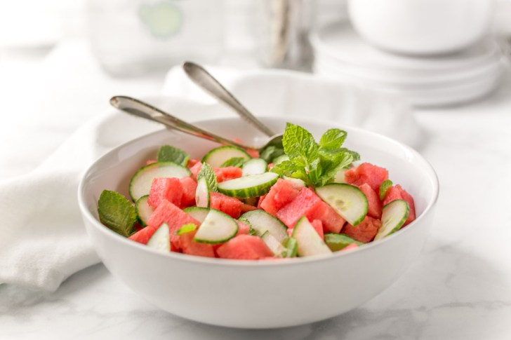 Watermelon Cucumber Fruit Salad Photo In a White Bowl With Serving Utencils