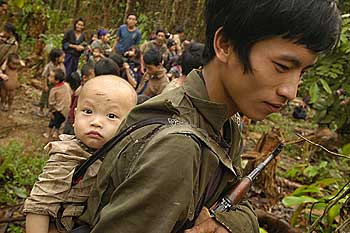 Song Tua Ya carries his AK-47 and young son while maintaining village security. (Photo: Roger Arnold / WorldPictureNetwork)