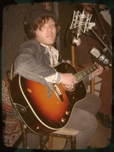 Greg Gilmore of The Kanes looking sedated while holding a guitar.