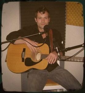 Adam Springob of the Kanes looking smug holding a guitar.