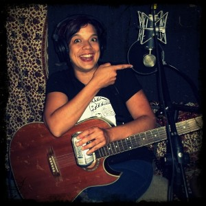 Penny Cillin of The Shames laughing and pointing at a microphone