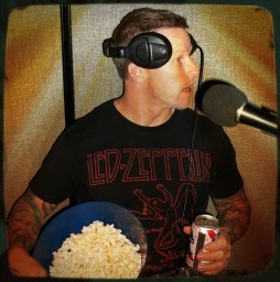 Jason Thomas with a surprised look on his face, holding popcorn and beer.