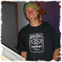 Evan Humphries, smiling and wearing a Reno Envy Whiskey Tshiry, standing next to an op-en oversized bible.