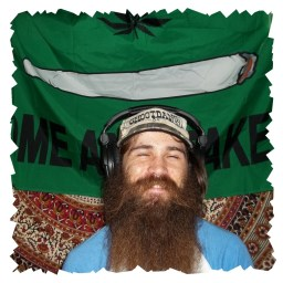 """John Underwood, Smiling through a very large beard and wearing a ball cap that says """"Shootdang"""" and sitting in front of a green banner with a lit joint that reads """"Come and take"""""""