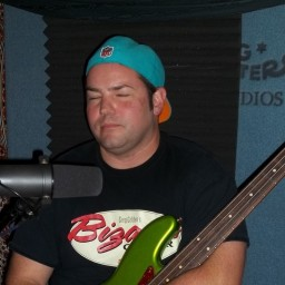 Travis Ambrose, holding his neon green bass with his eyes closed.