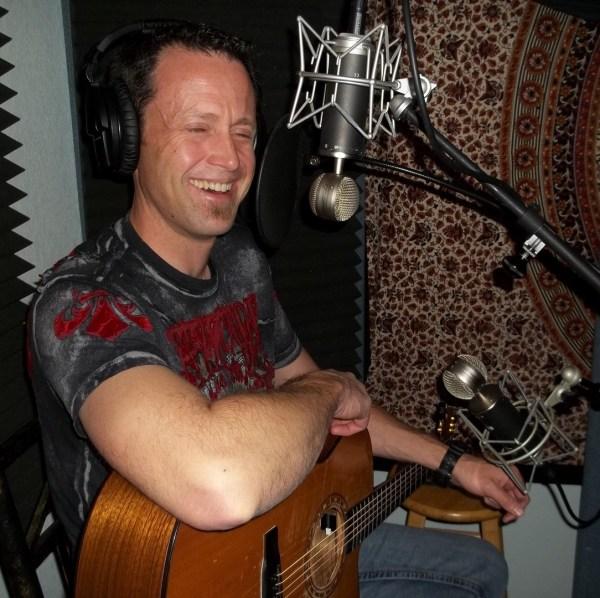 Todd Ballowe, Reno singer/songwriter, laughing while sitting with guitar