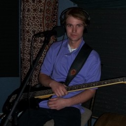 Gabe Hulse in a purple polo shirt holding his bass.