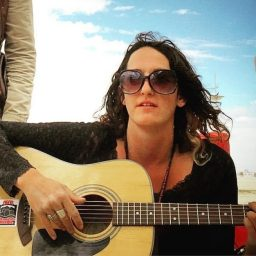 closeup of Mallory Mishler with a guitar in the desert